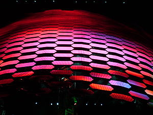 "U2 360° Tour - The video screen descends during a performance of ""The Unforgettable Fire"". The screen is made up of video panels affixed to a pantograph."