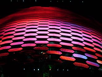 """U2 360° Tour - The video screen descends during a performance of """"The Unforgettable Fire"""". The screen is made up of video panels affixed to a pantograph."""
