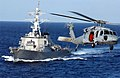US Navy 030217-N-0120R-003 An MH-60S Knighthawk helicopter flies by the guided missile destroyer USS John S. McCain (DDG 56).jpg