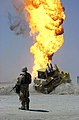 US Navy 030402-N-5362A-009 A U.S. Army soldier stands guard duty near a burning oil well in the Rumaylah Oil Fields in Southern Iraq.jpg