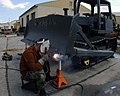 US Navy 030417-N-2306S-033 Steel Worker 3rd Class Robert M. Podorski from Toledo, Ohio, is attached to Naval Mobile Construction Battalion Twenty-Six (NMCB-26) welds an extension onto a bulldozer's earth moving blade.jpg