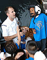 US Navy 031003-N-5821W-003 Aircrew Survival Equipmentman 1st Class Ryan Fitzgerald lets a first-grade student from Naval Air Station (NAS) Sigonella's Stephen Decatur Elementary School try on a helmet.jpg