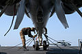 US Navy 040321-N-5781F-002 Plane Captain Airman Derek D. Eibensteiner, of Startell, Minn., tightens a tie-down chain on an F-A-18C Hornet assigned to the Royal Maces of Strike Fighter Squadron Two Seven (VFA-27) aboard the airc.jpg