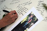 US Navy 040607-N-5362A-029 A mourner writes her condolences on a memory board for former President Ronald Reagan at the gate of the Ronald Reagan Presidential Library in Simi Valley, Calif.jpg