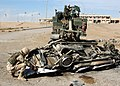 US Navy 041118-N-4388F-006 Construction Mechanic 2nd Class Thomas Tupling, assigned to Naval Mobile Construction Battalion Four (NMCB-4), attaches a tow cable to a demolished car prior to removing it from a street in Fallujah,.jpg