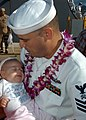 US Navy 041209-N-3019M-009 Storekeeper 1st Class George Moran, assigned to the Arleigh Burke-class guided missile destroyer USS Hopper (DDG 70), holds his newborn baby girl after returning from a six-month deployment in support.jpg