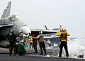 US Navy 050308-N-0535P-252 An Aviation Boatswain's Mate guides an F-A-18A- Hornet onto a catapult prior to launch from the Nimitz-class aircraft carrier USS Harry S. Truman (CVN 75).jpg