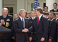 US Navy 050420-N-0000A-001 President George W. Bush shakes hands with U.S. Naval Academy Head Football Coach Paul Johnson during a ceremony at the White House.jpg