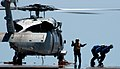 US Navy 050529-N-7130B-073 An aircraft director signals two flight deck crews members away the spinning rotors of an MH-60S Knighthawk.jpg