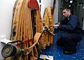 US Navy 050708-N-1397H-002 Aviation Electronics Technician 3rd Class Brad Delabruere assigned to the amphibious assault ship USS Peleliu (LHA 5) restores a fire hose after completing periodic maintenance on a fire station.jpg
