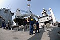 US Navy 071118-N-0193M-797 Boatswain's Mate 1st Class Jay Collette, directs the crane operator to lift the truck higher, while members of deck department unload vehicles and equipment from the hull of the amphibious dock landin.jpg