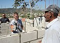 US Navy 080209-N-2392S-060 Aviation Warfare Systems Operator 2nd Class Adam Corner, assigned to Patrol Squadron 46 (VP-46), jokes with a local Salvadoran working with him on a Habitat for Humanity home.jpg