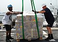 US Navy 080825-N-4044H-062 Boatswain's Mate 3rd Class Anthony Murphy and Chief Electronics Technician David Close prepare a pallet of humanitarian assistance supplies on the weather deck aboard the guided-missile destroyer USS.jpg