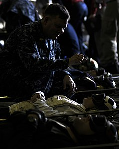 US Navy 110511-N-GZ277-096 Chaplain Lt. Cmdr. James West prays for Sailors during a mass casualty drill in the hangar bay of USS Carl Vinson (CVN 7.jpg