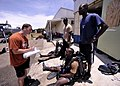 US Navy 110729-N-KB666-092 Master Seaman John Penney, left, onducts pre-dive checks with Ordinary Seaman Kemar Smith, sitting left, Petty Officer D.jpg