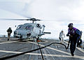 US Navy 111206-N-ZF681-254 Gas Turbine System Technician Mechanical Fireman Matthew Horn moves a fuel line away from an SH-60B Sea Hawk helicopter.jpg