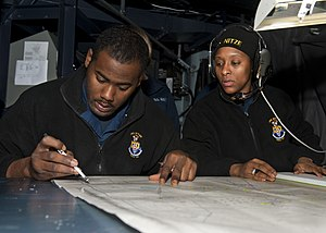 US Navy 111212-N-FI736-058 Operations Specialist 3rd Class Bryan Sherman, plots the ship's location as Operations Specialist 1st Class Teah Owens,.jpg
