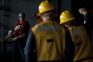 US Navy 120202-N-DR144-198 Boatswain's Mate Seaman Payne Ivie listens to commands from rig captains while manning a line in the hangar bay aboard t.jpg