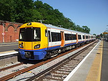 A London Overground train waiting at a platform in the station.