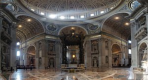 St. Peter's Basilica VATICAN. Wide angle photo of interior. Details visible in this view include: a golden band of text that extends around the cornice, niches with statues in every pier, carved angels around the arches, and the inlaid marble floor, the design of which radiates from the baldachin under the dome.