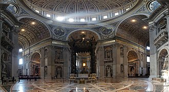 Wide angle photo of interior. Details visible in this view include: a golden band of text that extends around the cornice, niches with statues in every pier, carved angels around the arches, and the inlaid marble floor, the design of which radiates from the baldachin under the dome.