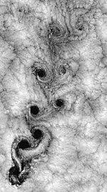 Satelitobildo de padrono de nuboj formiĝantaj de tumulto ĉe la pli malalte forlasis kaŭzantan serion de kirlado de nubvorticoj kiu iom post iom disipas kiam ili moviĝas al la supra rajto