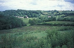 Green rolling hills with a cluster of houses and a church left of centre.