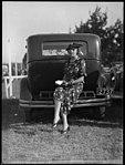 Woman sitting on bumper bar of a car at Warwick Farm racecourse (3655609569).jpg