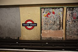 WoodGreen - Roundel and poster on westbound platform before (4571350778).jpg