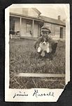 """Jimmie Russell""- photograph of young boy holding a small dog outside a wooden house. (8512972159).jpg"