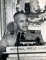 """Middle-aged man wearing U.S. Navy khaki uniform and Captain shoulder epaulettes standing behind a lectern with microphone and placard that reads """"National Press Club."""""""