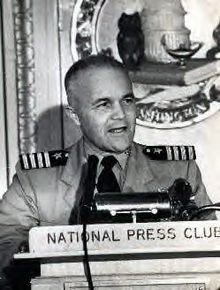 "Middle-aged man wearing U.S. Navy khaki uniform and Captain shoulder epaulettes standing behind a lectern with microphone and placard that reads ""National Press Club."""