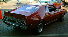 Shows the rear right of a 1973 AMC Javelin Pierre Cardin edition finished in red