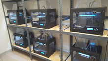 Several 3-D printers in enclosures on shelves