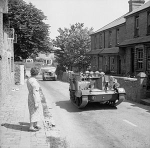 55th (West Lancashire) Infantry Division - Universal Carriers of the 9th Battalion, King's Regiment (Liverpool), of 164th Brigade, moving through a Sussex village, 3 July 1941.