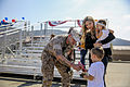 A U.S. Sailor, left, with the Marine Corps 1st Battalion, 5th Marine Regiment, assigned to Marine Rotational Force-Darwin, exchanges greetings with friends and family members during a homecoming event at Marine 141020-M-SE196-004.jpg