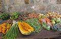 A table with vegetables for sale outside the Market in Charlestown, Nevis, West Indies, up against a cut-stone wall.JPG
