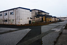 A series of large concrete buildings with peeling paint, clearly in a state of disrepair