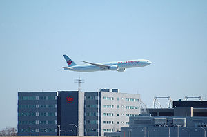 Montréal–Pierre Elliott Trudeau International Airport - An Air Canada Boeing 777-300ER performing a fly past, with Air Canada's corporate headquarters in background.