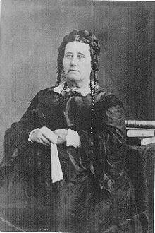 Portrait of an unsmiling, middle-aged woman in a voluminous dress. Her hair is piled on the back of her head, with ringlets near her ears. She holds a fan in her hands.