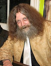 An older caucasian male with long, thick hair and matching beard, sits facing the camera.