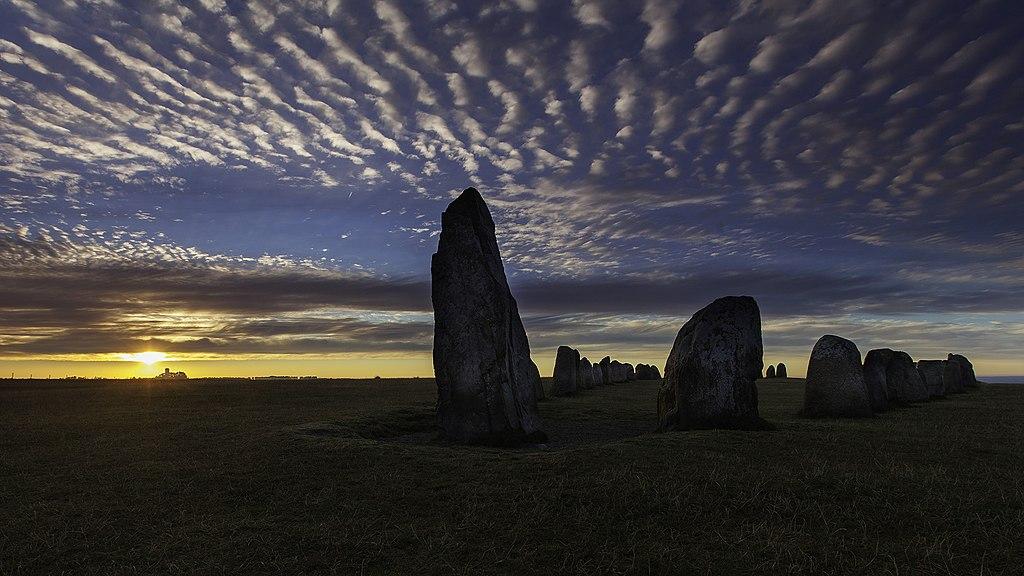 Skeppssättningen Ales stenar i soluppgång under en molnig himmel