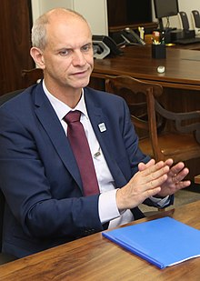 Middle-aged man with short hair speaking during a meeting. He is wearing a dark blue suit, with a white shirt and wine-colored neck tie.