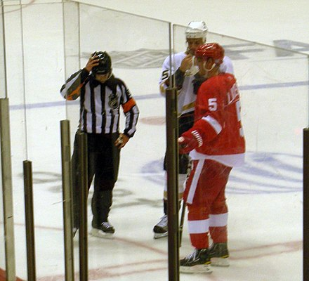 Captains Nicklas Lidstrom of the Detroit Red Wings (right) and Ryan Getzlaf of the Anaheim Ducks (middle) talk with a referee. Anaheim Ducks vs. Detroit Red Wings Oct 8, 2010 44.JPG
