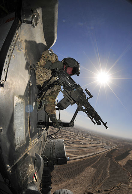 Army Spc. Richard Burton, crew chief with the 25th Infantry Division, provides security in a Black Hawk helicopter during a flight mission over Afghanistan's Kandahar province, 26 Nov. 2012.