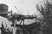 A soldier lies amongst the grass in the prone position behind a machine gun which he is holding in the shoulder.