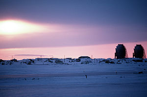 The sun sets behind a radar station. The stati...
