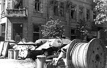 Poles erected barricades, such as this one on Napoleon Square, throughout Warsaw, making it difficult for German infantry and tanks to operate. In background: captured Hetzer tank destroyer.