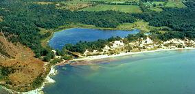 Aerial photograph of a lakeshore, a sandy barrier beach, and a pond behind it; the photograph appears to have been taken in summer, since the land around the pond is green with foliage. There are high, forested sand dunes on the barrier beach.