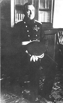 A man seated, wearing a dark uniform with two rows of buttons, with his peaked cap on his lap